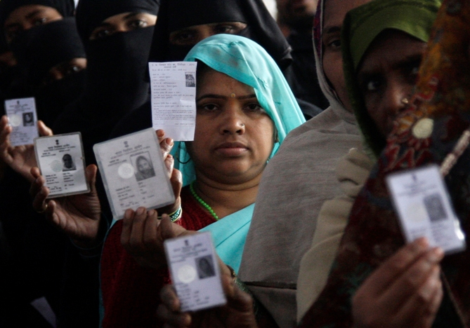 Voters display their voter identity cards as they wait for their turn to cast their ballot at a polling station.