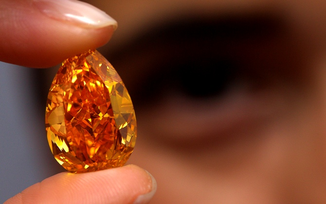 A Christie's member of staff displays 'The Orange', the world biggest orange diamond, which weighs 14.82 carats during an auction preview. Photographs: Denis Balibouse/Reuters