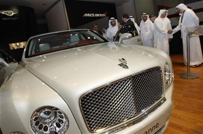 Dubai's deputy ruler Sheikh Maktoum bin Mohammed bin Rashid al-Maktoum (3rd L) tours Bentley's display with other officials at the Dubai International Motor Show.