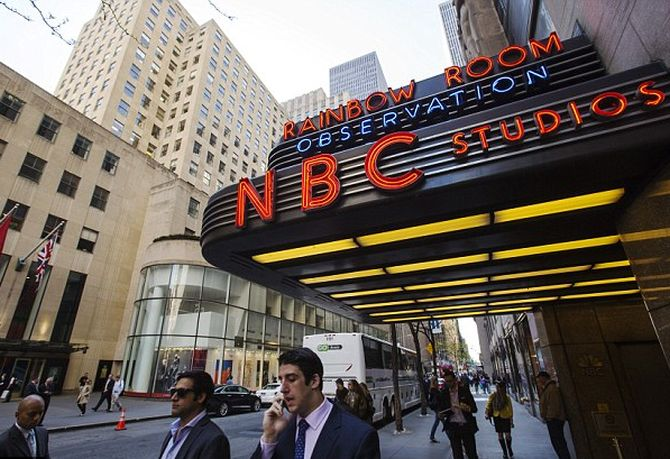 Pedestrians walk past the entrance to the NBC studios, outside Rockefeller Center.