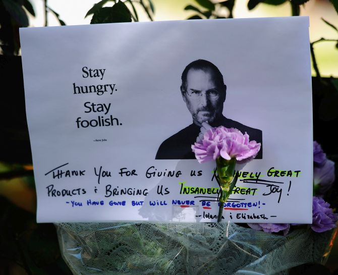 A make shift memorial for Steve Jobs is seen on the sidewalk outside his home.