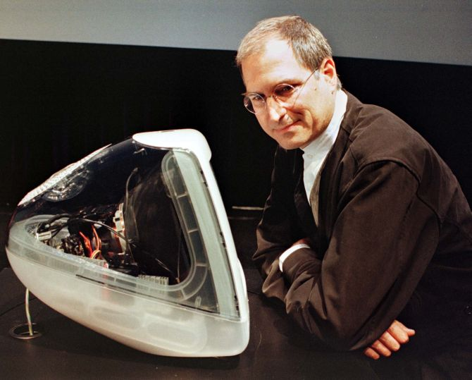 Steve Jobs standing next to the iMAC DV Special Edition that is encased in a clear graphite colour.
