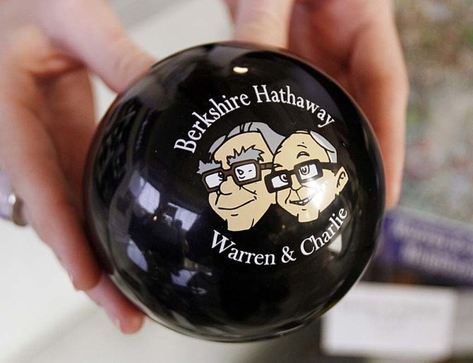A clerk holds a magic answer ball featuring images of Berkshire Hathaway Chairman Warren Buffett (L) and Vice-Chairman Charlie Munger at the company's annual meeting weekend in Omaha.