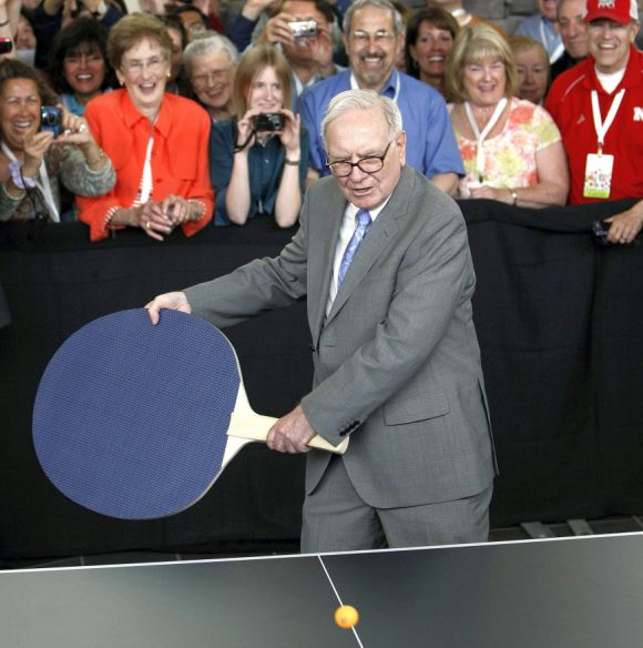 Berkshire Hathaway chairman Warren Buffett plays table tennis with a world champion using a giant paddle at the Berkshire Hathaway annual meeting weekend in Omaha.