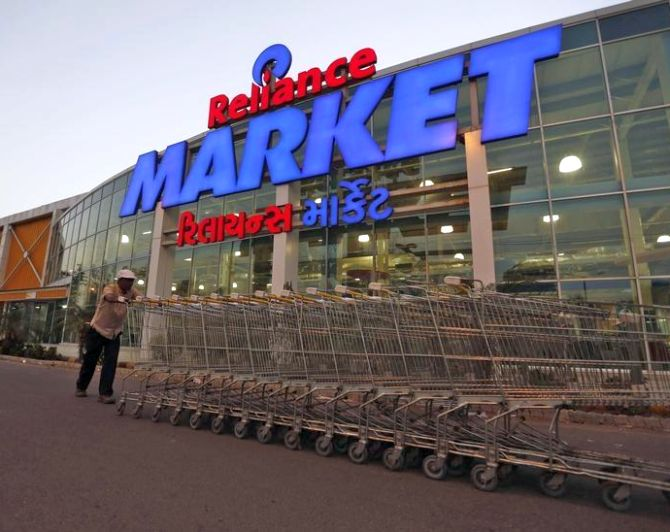 A worker pushes trolleys outside the Reliance Market superstore in the western Indian city of Ahmedabad.