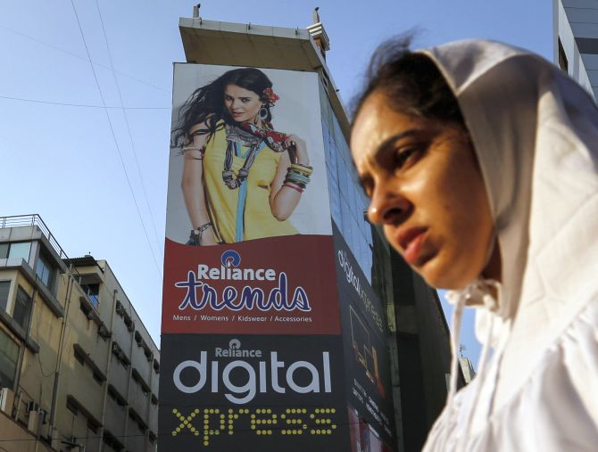 A woman walks past a Reliance Trends mall at a shopping district in Mumbai.
