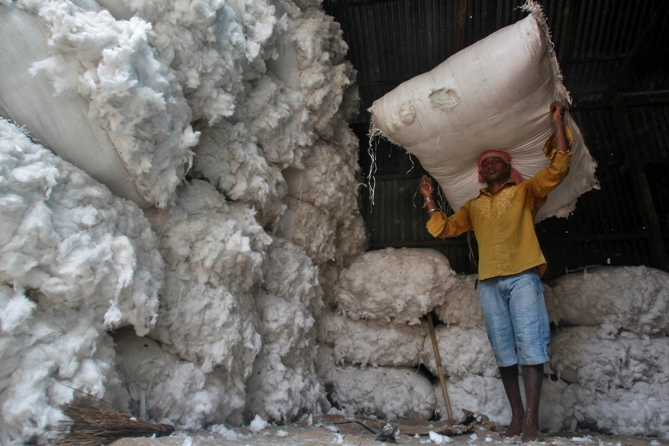 A worker carries a sack filled with cotton at a wholesale cotton market in Agartala.