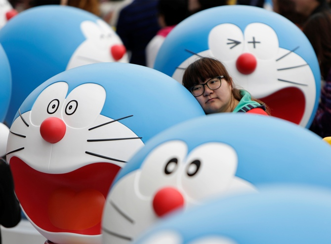A visitor poses for a photo next to a Doraemon model during an exhibition in Beijing.