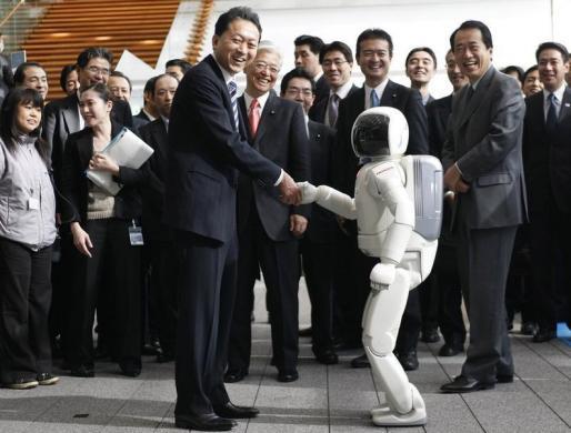 Yukio Hatoyama shakes hands with Asimo.
