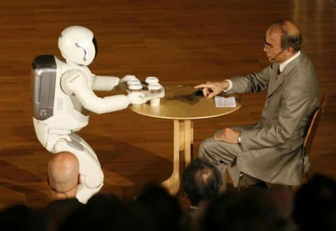Asimo serves some drinks during a presentation at the university of Bielefeld during its first appearance in Germany.