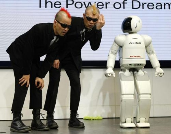 Japan's mime artists HIRO-PON and Ketch performs with Honda Motor's humanoid robot Asimo.