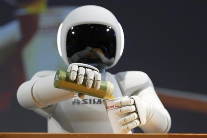 Asimo pours a drink into a cup during a news conference at the 42nd Tokyo Motor Show in Tokyo.