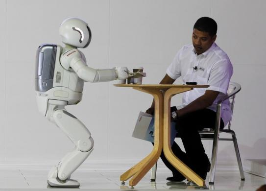 Asimo serves tea to a visitor during the Johannesburg International Motor Show at Nasrec in Johannesburg.