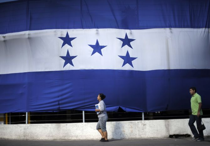 A woman and a man walk past a giant Honduran flag in Tegucigalpa.