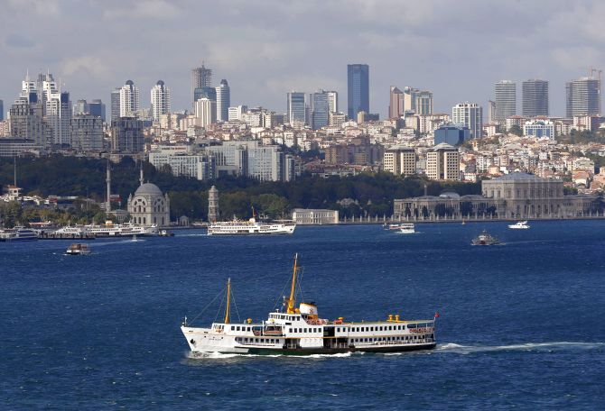 A ferryboat moves along the Bosphorus and past the city's skyscrapers (rear) in Istanbul.
