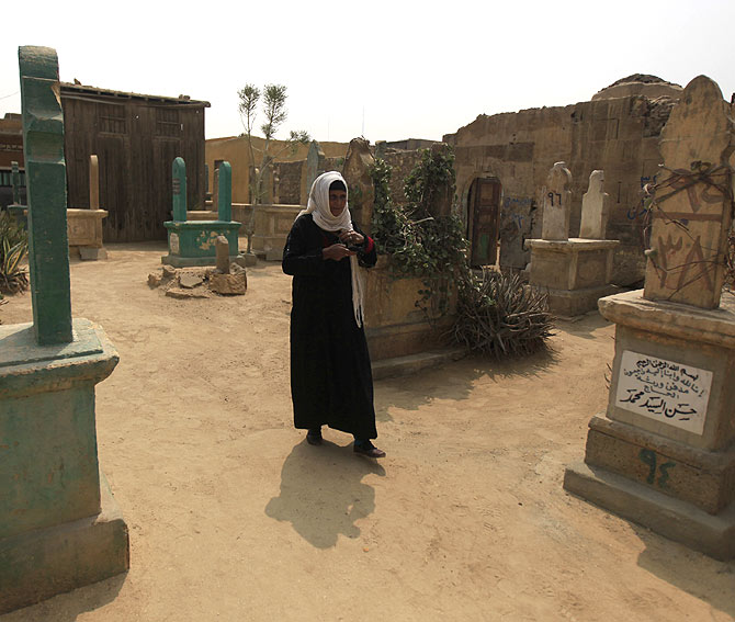 A woman walks near tombs in front of her home.