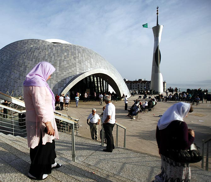 Muslims walk near a mosque.