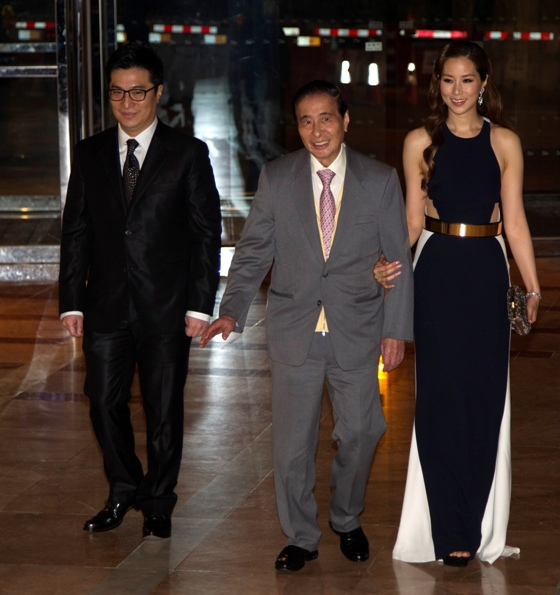 Hong Kong tycoon Lee Shau Kee (C), Martin Lee Ka-Shing (L) and his wife Cathy Chui attend a wedding ceremony.