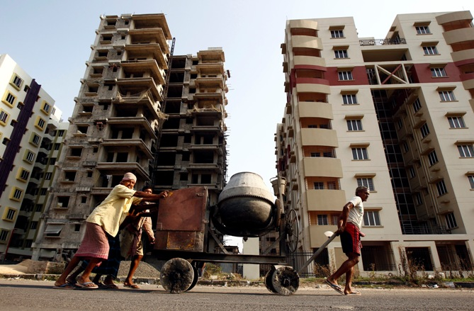 Labourers move a concrete mixer past under construction site of residential buildings in Kolkata.