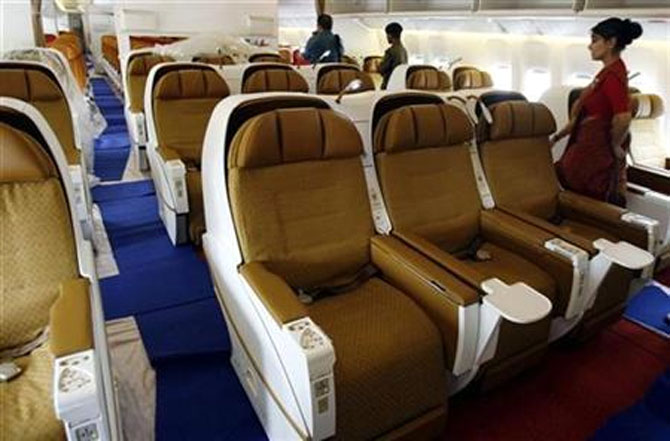People walk inside the business class section of Air India's Boeing 777-200 LR aircraft.
