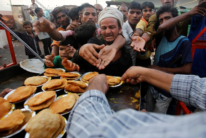 People reach out their hands as they wait to receive food provided by a charitable organisation outside a temple in New Delhi.