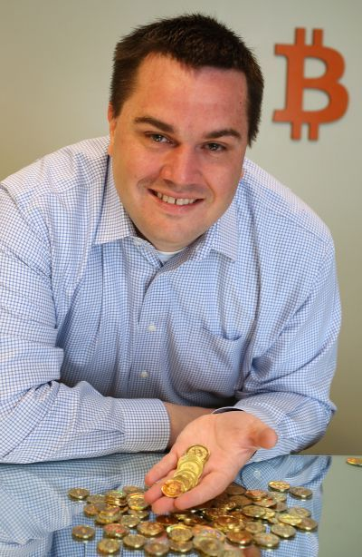 Software engineer Mike Caldwell holds physical Bitcoins he minted in his shop.