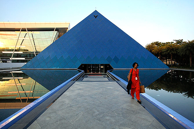 n employee walks out of an iconic pyramid-shaped building made out of glass in the Infosys campus.