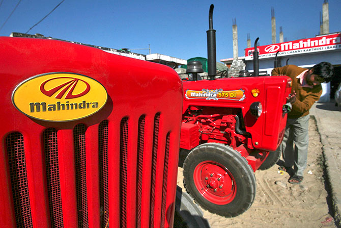 A worker cleans a Mahindra tractor outside its showroom on the outskirts of Jammu.