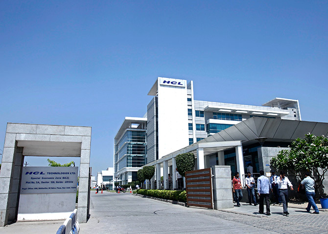 People walk in front of the HCL Technologies Ltd office at Noida, on the outskirts of New Delhi.