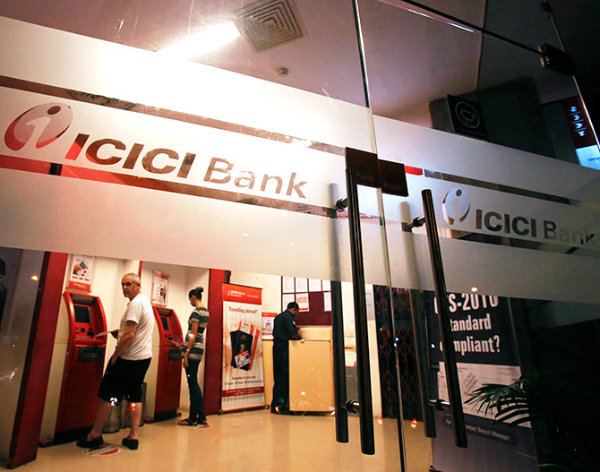 Customers use ATM machines at an ICICI Bank branch in Mumbai.