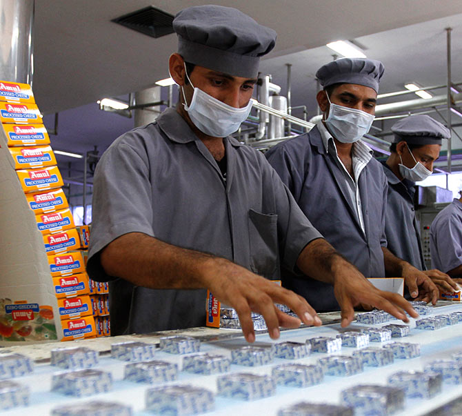 Workers pack processed cheese cubes during a media tour to Amul satellite dairy in Khatraj village.