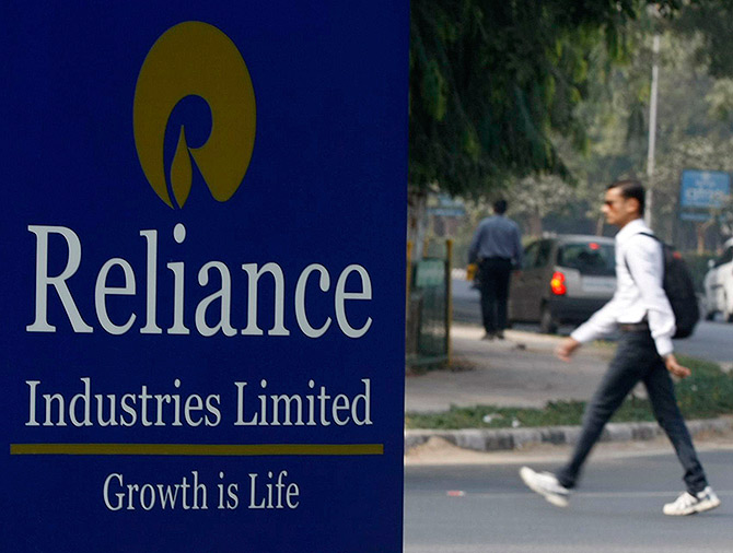 A man walks past a Reliance Industries Limited sign board installed on a road divider in the western Indian city of Gandhinagar.