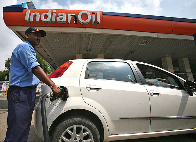 A worker fills a car with diesel at a fuel station in Jammu.