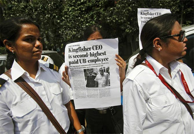An employee of Kingfisher Airlines holds a poster during a protest against the company near the domestic airport in Mumbai.