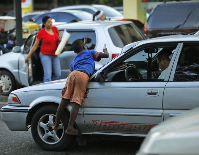 An immigrant child from Haiti cleans the windshield of a car before asking for money on the streets of Santo Domingo.