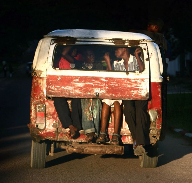 Congolese children sit on a back of a car in Kinshasa.