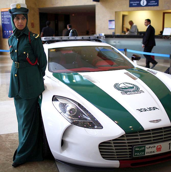 A police officer stands near an Aston Martin car used by Dubai police.