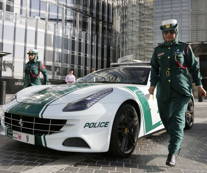 Police officer Badrya Salem AlSowaidi walks near a Ferrari police car.