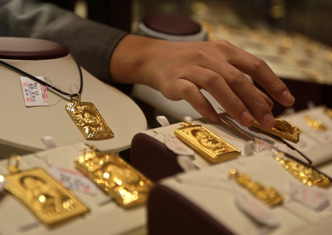 A sales assistant puts back a gold Buddha-shaped pendant after showing to a customer at Caibai Ornaments store in Beijing.