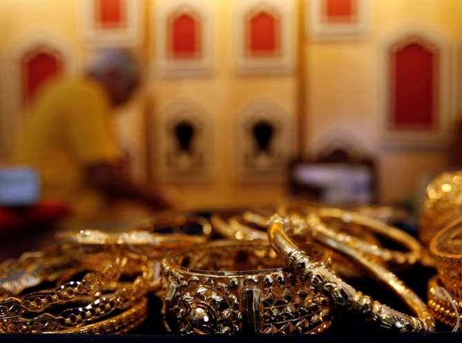 A gold jewellery shop owner arranges ornaments at a counter in Kolkata.