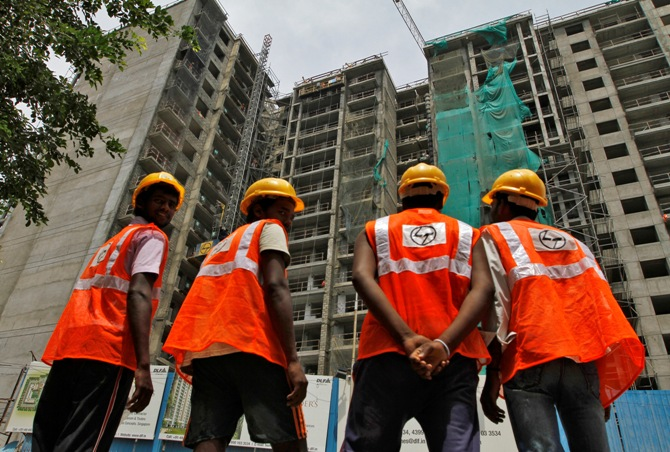 Construction workers stand in front of a residential building under construction in Chennai.