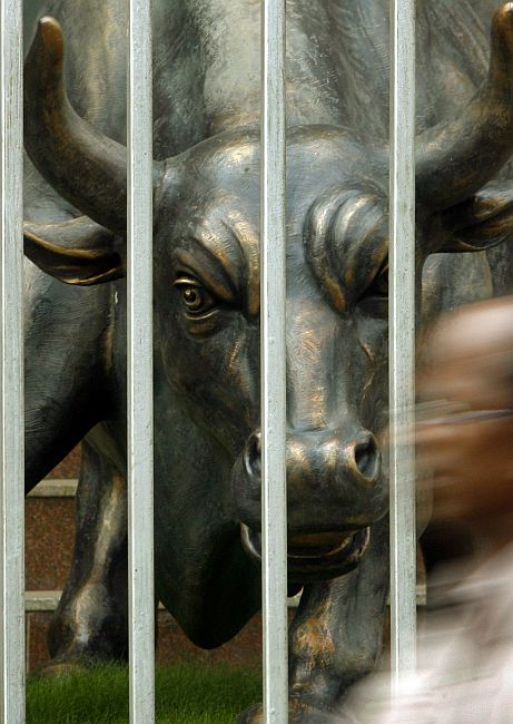 A man walks past a bronze statue of a bull outside the Bombay Stock Exchange.