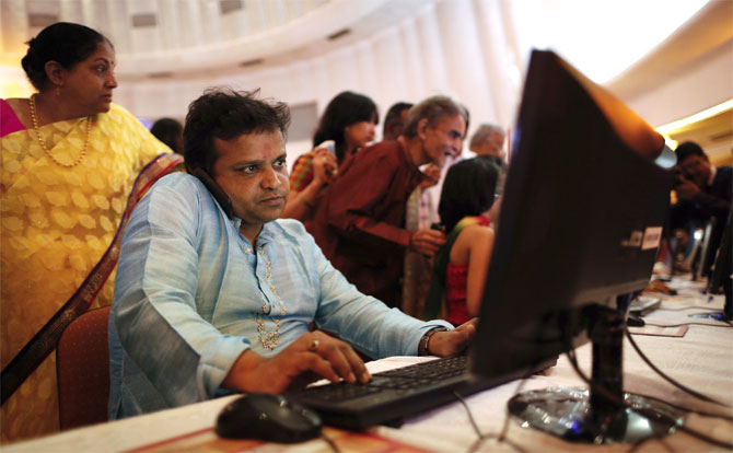 A stockbroker speaks on phone while trading at a terminal during the Diwali special trading session.