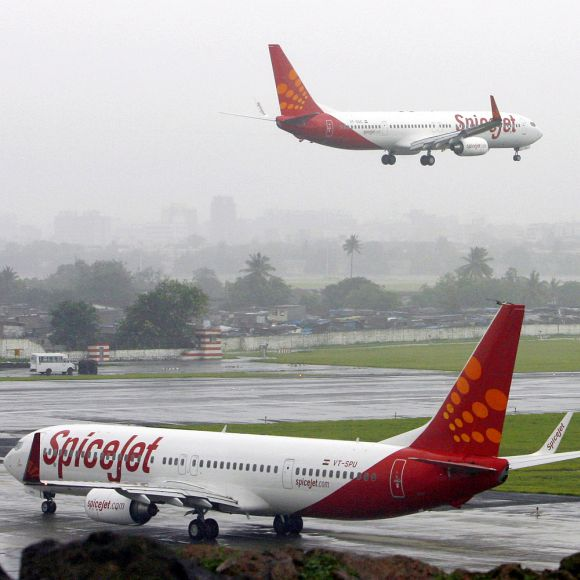 India's SpiceJet aircrafts prepare for landing and take-off at the airport in Mumbai.