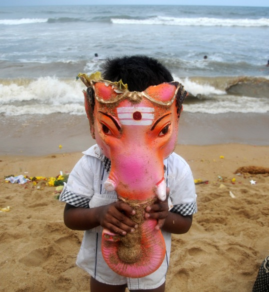 A boy wears the head of an idol of Ganesh, deity of prosperity, during immersion of the 10-day-Ganesh Chaturthi, in Chennai September 15, 2013.