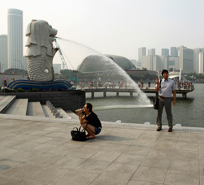 Tourists take photos of the Merlion in the hazy skyline of Singapore.