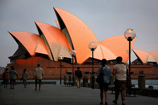 People look at the Sydney Opera House as they walk past at sunset.