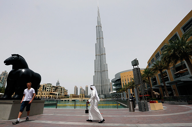 An Emirati man walks past a tourist posing for a photo near the Burj Khalifa, the tallest tower in the world, in Dubai.