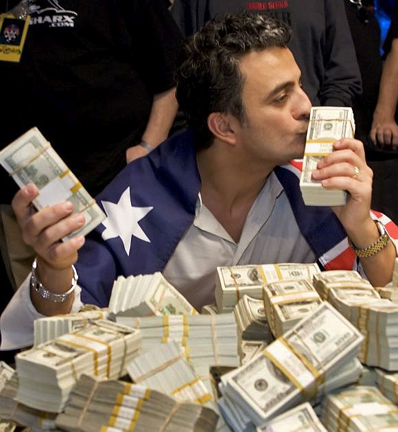 Joseph Hachem kisses a stack of $100 bills after winning World Series of Poker.