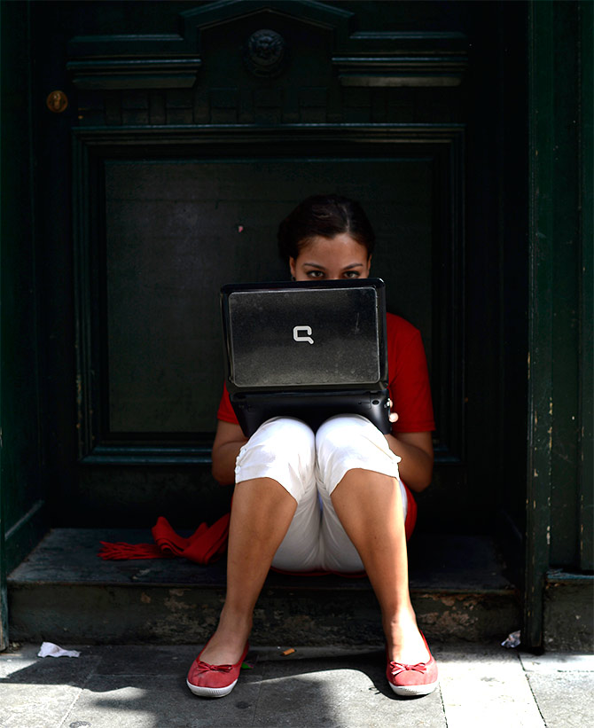 A girl wearing the traditional red and white festival costume uses a laptop computer.